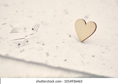 Wooden heart on handmade paper with music notes.