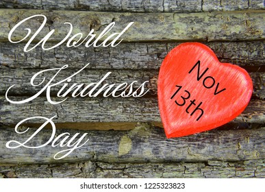 Wooden heart on rustic wooden background. The heart is painted red. Message has been added for World Kindness Day on November 13th