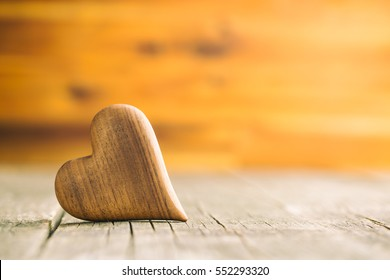 The wooden heart on wooden table.
