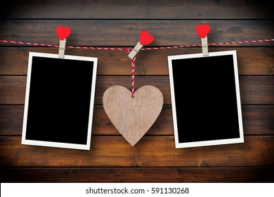 Wooden heart and two empty photo frames on a rustic wooden background as love concept for valentines day