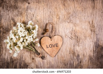 Wooden heart and white flowers on an old wooden board. Backgrounds and textures. St. Valentine's Day.