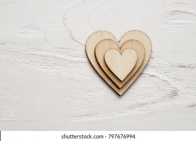 Wooden hearts on white wooden background