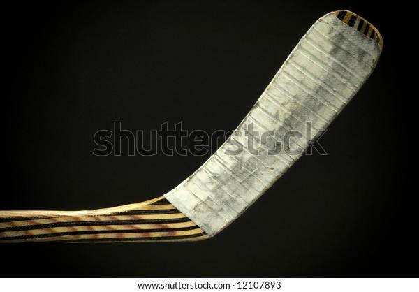 Wooden hockey stick on black background