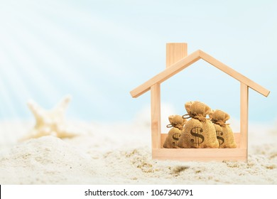 Wooden home model and money bag put on the beautiful sand and starfish on blue sky background in summer vacation, Saving or loan for buy a new house or real estate owner concept.