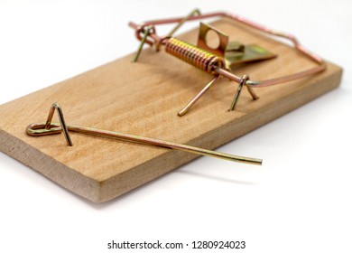 Wooden home mousetrap on a white background. Selective focus. Closeup of an unloaded mouse trap. Empty mousetrap worked.
