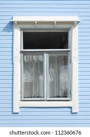 Wooden home window decorated with lacy curtain