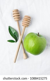 Wooden Honey Dippers Ripe Green Apple Leaves on White Cotton Linen Fabric Background. Organic Cosmetics Ayurveda Healthy Lifestyle Skin Care Concept. Flat Lay with Copy Space