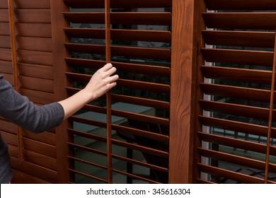 Wooden horizontal blind, Close , women hand