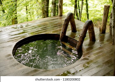Wooden hot tub outdoors.close up photo.wooden bath in the forest. water treatment on landscape. water, health, wellness, relaxation concept