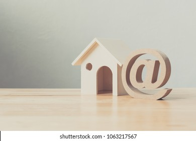Wooden house and address sign on wood table. Email contact us concept