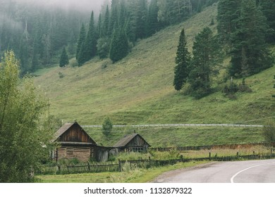 Wooden house with barn behind fence near foot of mountains and asphalt highway in gloomy weather. Mist floats on mountain peak with coniferous trees. Pines and spruces on mountainside. Rural landscape