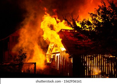 Wooden house or barn burning on fire at night.