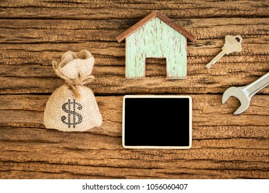 Wooden house and blackboard for ad text and money bag and key and wrench put on the old wood, Saving money and loan for construction real estate and home concept.