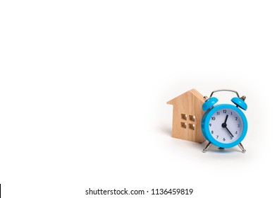 Wooden house and blue alarm clock on a white background. The concept of rent housing monthly and hourly. Temporary affordable accommodation, hotels and hostels. A loan to buy a house.