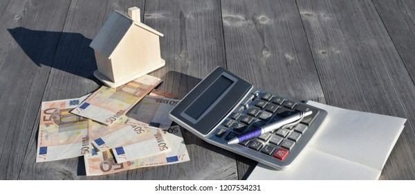 Wooden house, calculator and 50 euro banknotes on grey table background with copy space for text outdoors in sunlight with shadows.  House building, buying or renting new home planning concept.