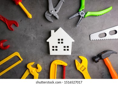 Wooden house and construction tools toy on stone pattern background with copy space.Home Repair concept, Repair maintenance concept, Renovation concept