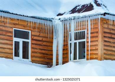 Wooden house covered with snow and icicles. Winter in Russia.