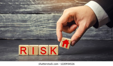wooden house and cubes with the word risk. The concept of risk, loss of real estate. Property insurance. Loans secured by home, apartment. Financial risks, litigation. Confiscation for debt