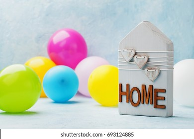 Wooden house decorated hearts and air balloons on blue background. Housewarming party, gift, real estate or buying a new home concept.