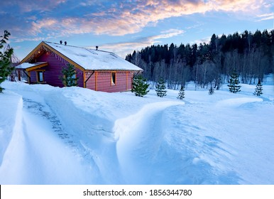 Wooden house at edge of forest. One-storey cottage in winter weather. Single private house near forest. Country house. Trail goes to cottage in middle of snowdrifts. Cottage on a sunny winter day