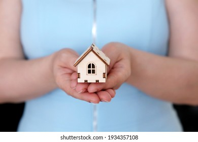 Wooden house in female hands, real estate agent. Woman with house model, concept of insurance, housekeeper, purchase or rental home