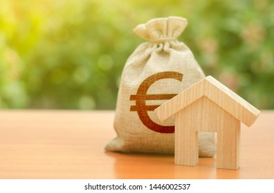 Wooden house figurine and Euro money bag on the background of nature. Budget, subsidized funds. Mortgage loan for the purchase of housing, construction or modernization. Tax, building maintenance.