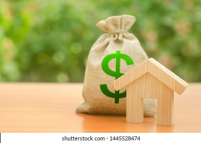 Wooden house figurine and money bag on the background of nature. Mortgage loan for the purchase of housing, construction or modernization. Budget, subsidized funds. Tax policy, building maintenance.
