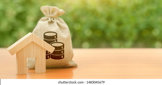 Wooden house figurine and a money bag. Family budget, control and reduction of expenses. subsidized funds. Mortgage loan for purchase housing, construction or modernization. Tax, building maintenance.