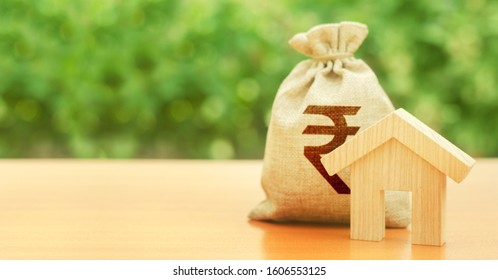 Wooden house figurine and money bag with indian rupee INR symbol. Budget, subsidized funds. Mortgage loan for purchase housing, construction or modernization. Tax, building maintenance.