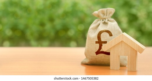 Wooden house figurine and pound sterling money bag on the background of nature. Budget, subsidized funds. Mortgage loan for purchase housing, construction or modernization. Tax, building maintenance.