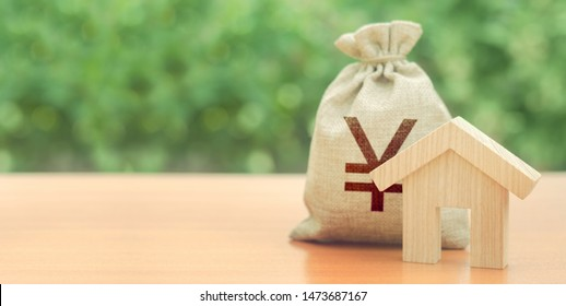 Wooden house figurine and Yen or yuan money bag. Budget, subsidized funds. Mortgage loan for purchase housing, construction or modernization. Tax, building maintenance. China, Japan