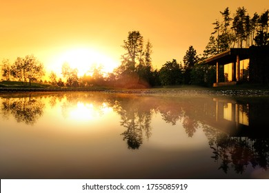 wooden house in forest landscape with scenery reflections in lake water at sunset against setting sun background. Natural color of nature at dusk. Ground wide view