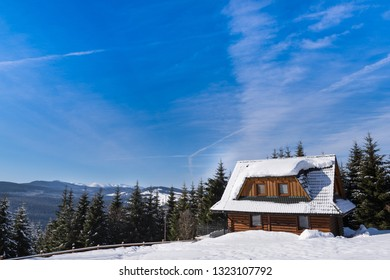 Wooden house in the forest. Snowy hills in European countryside at sunny day