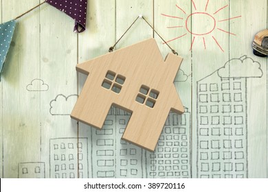Wooden house hanging on green wood wall, with sun clouds buildings doodles background.