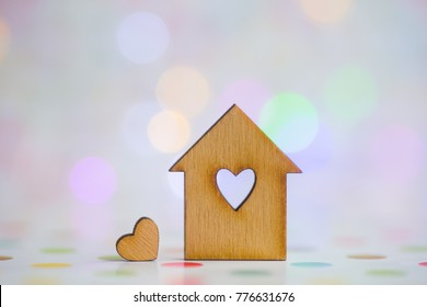Wooden house with hole in form of heart with little heart on colorful bokeh background. Concept of sweet home.