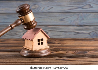 wooden house, judge's gavel on wooden background. purchase, sale of real estate. housing