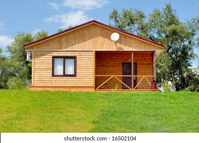 The wooden house with a lawn on a background of the blue sky