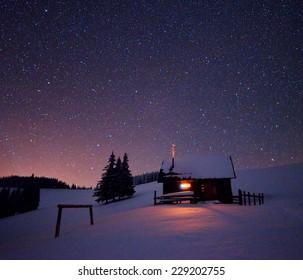 Houten huis met een licht in het raam. Nachtlandschap in de winter