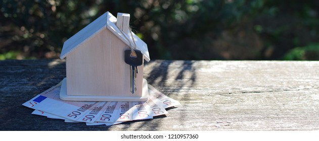 Wooden house model and 50 euro currency banknotes on grey weathered table background with copy space outdoors in sunlight with shadows. House building, buying or renting new home planning concept.