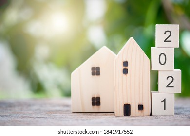 Wooden house model with wooden block number 2021 and copy space using as background concept to save money buying house, new year property, business, real estate and property concept.