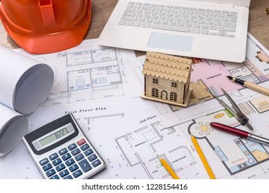 Wooden house model with blueprint and laptop
