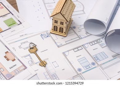 Wooden house model and key on house plan drawing