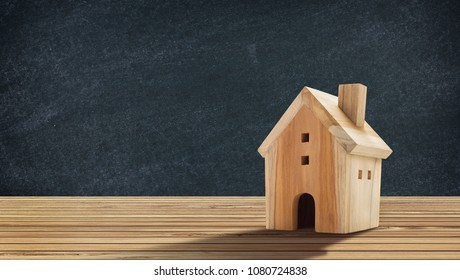 Wooden House Model on wooden floor with blackboard texture background there is copy space.Home,Housing and Real Estate concept.