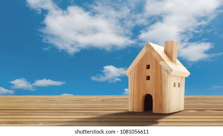 Wooden House Model on wooden floor with blue sky background there is copy space.Home,Housing and Real Estate concept.