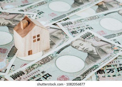 Wooden house model on pile of Japanese yen banknotes. Real estate concept.