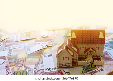 wooden house model on pile of euro banknote ,yellow day light background