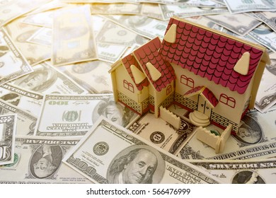wooden house model on pile of dollar banknote ,yellow day light background