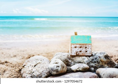 Wooden house model on the rock with blurred seascape background, Christian concept from bible, wise man built  house on the rock