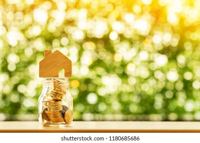 Wooden house model put on the bottle with gold coin inside on sunlight in the public park, Saving money or loan for business investment real estate or buy a new home for a family concept.