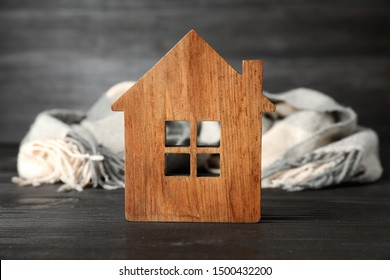 Wooden house model and scarf on grey table. Heating efficiency